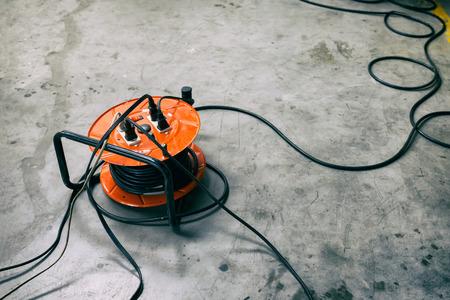 Foto de Cable reel Orange color Be plugged with Black Cable Wire Placed on the floor. - Imagen libre de derechos