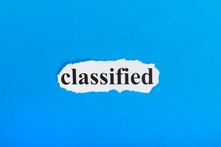 Photo for classified text on paper. Word classified on torn paper. Concept Image. - Royalty Free Image