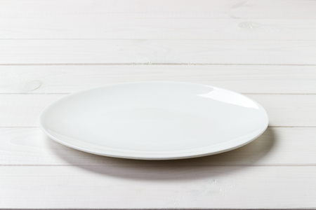 Foto de White Round Plate on white wooden table background. Perspective view. - Imagen libre de derechos