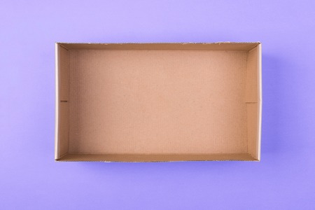 Foto de empty cardboard paper box on purple background. delivery concept, top view. - Imagen libre de derechos