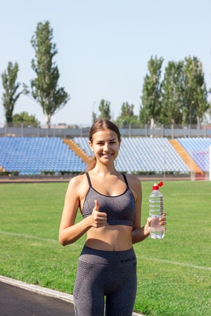 Photo for Portrait of happy female athlete holding a bottle of water and thumb up on the stadium. Sports and healthy concept. - Royalty Free Image
