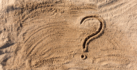 Foto de question marks written on beach sand close up, with copy space. - Imagen libre de derechos