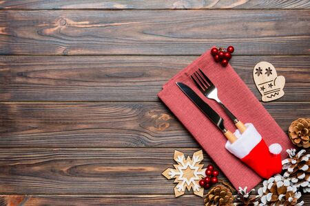 Foto de Top view of fork and knife on napkin on wooden background. Different christmas decorations and toys. New Year dinner concept with empty space for your design. - Imagen libre de derechos