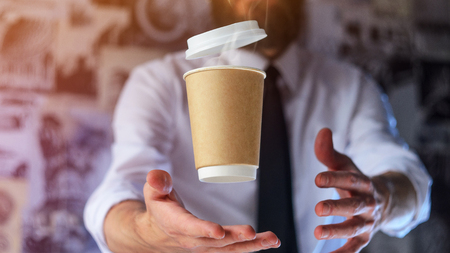 Foto de Barista in a white shirt with a tie holds floating in the air a paper cup with a hot drink on his outstretched arms. Barista wizard concept. Background for advertising and placing logo on your drink - Imagen libre de derechos