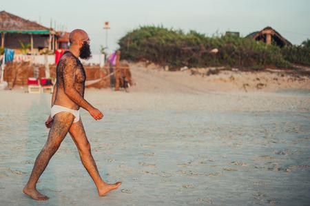 Foto de Unknown white walks on Indian beach during sunset. Hairy body. A man with a beard - Imagen libre de derechos
