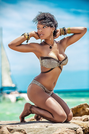 Foto de Beautiful curly mulatto in bracelets and bikinis at the sea - Imagen libre de derechos