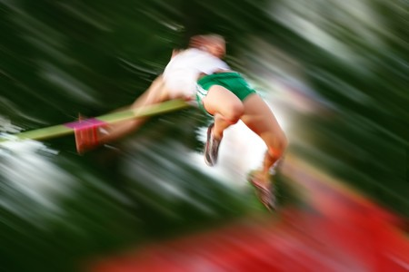 Motion blur of a high jumper going over the bar
