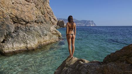 Photo pour A shot of beautiful young womans back in black bikini swimwear, outdoor stock footage - image libre de droit