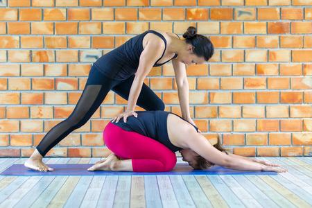 Foto de Asians female trainer helping young woman doing yoga. - Imagen libre de derechos