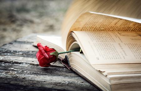 Foto de closed book on wood desk with rose - Imagen libre de derechos
