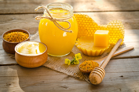 Photo pour two wooden bowls one with honey another with pollen.The bank of honey stay near honeycombs,wax,wooden spoon with honey and dipper - image libre de droit