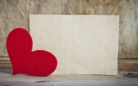 Foto de the form for a card on wooden background .   handmade heart from red felt is  in the left corner of the form - Imagen libre de derechos