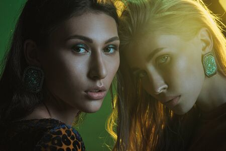 Foto de Fashion photo session in the studio. Two beautiful woman models. Blonde and brubette. Yellow leopard dress. Studio racks and flashes. Yellow and green background. - Imagen libre de derechos