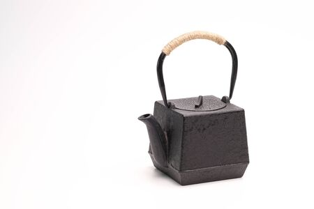 Black metal cast-iron traditional teapot on a white background.