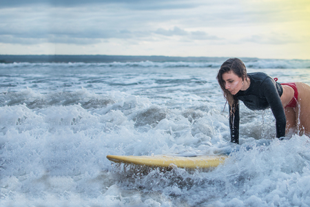 Photo for action of young woman try to step standing on the surfboard in the med of the ocean. - Royalty Free Image