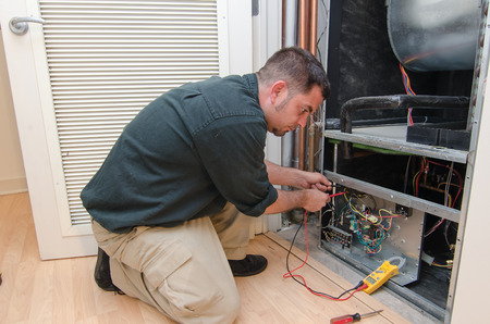 Photo pour HVAC technician working on a residential heat pump - image libre de droit