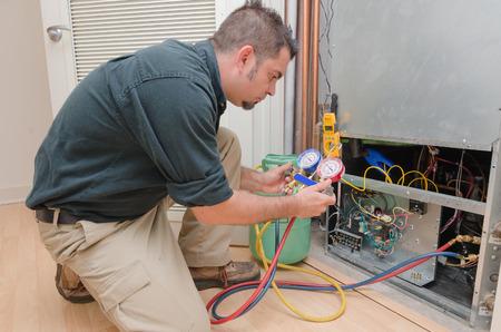 Photo pour HVAC technician charging a heat pump with refrigerant - image libre de droit