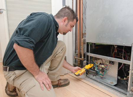 Photo for HVAC technician using a meter to check heat pump amperage - Royalty Free Image