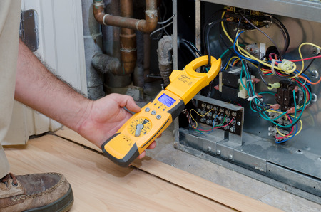 Foto de HVAC technician checking the amperage on a residential heat pump - Imagen libre de derechos