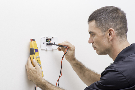 Foto de Trained HVAC technician checking troubleshooting a thermostat - Imagen libre de derechos