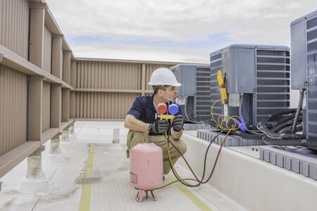 Photo for HVAC service technician charging a condensing unit with 410A refrigerant - Royalty Free Image