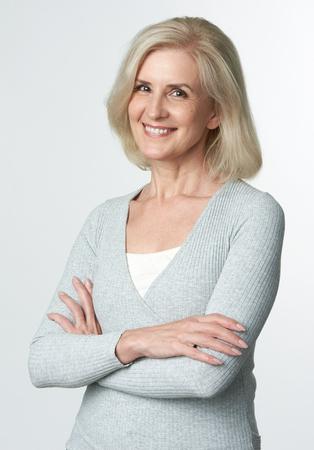 Foto de Cheerful mature blonde woman. Studio portrait isolated on grey background - Imagen libre de derechos