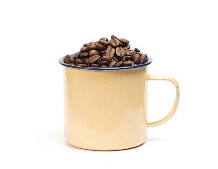 Foto de Coffee beans in a retro enameled mug isolated on white - Imagen libre de derechos