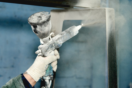 Foto de A man produces powder paint metal products.A man works in a mask. - Imagen libre de derechos