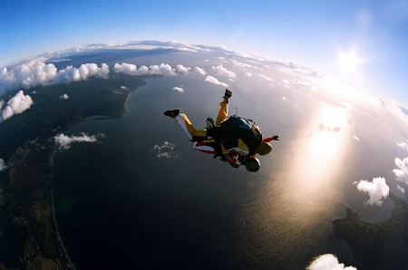 Portrait of two tandem skydivers in action parachuting through the air.