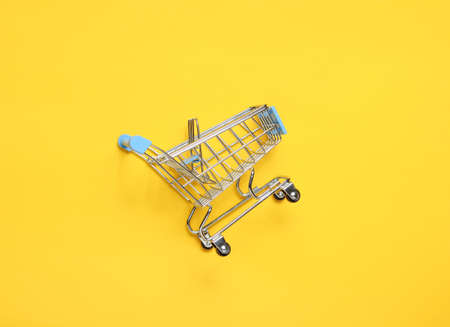 Mini shopping trolley for shopping on yellow background, consumer concept, minimalism, top view.