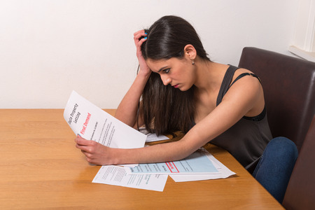 Photo for young student worried over un-paid bills and student loan - Royalty Free Image