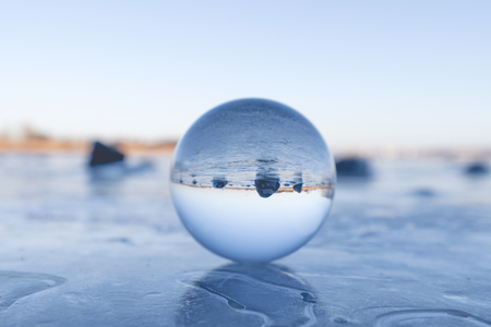 Foto de Crystal ball on a frozen lake in the winter with black rocks in the background - Imagen libre de derechos