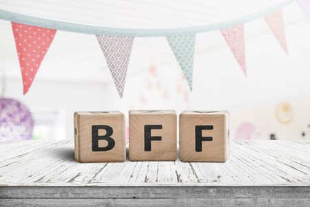 Photo for BFF greeting message made of wooden blocks with colorful flags hanging above - Royalty Free Image
