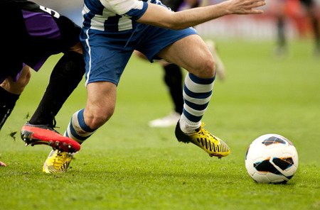 Photo for Legs of two soccer players vie on a match - Royalty Free Image
