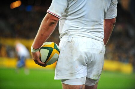 A rugby player holds the ball as he stares across the field.