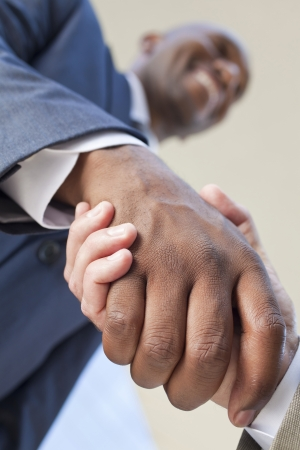 African American businessman or man shaking hands with a caucasian colleague doing a business deal