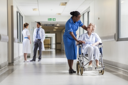 Foto de Senior female woman patient in wheelchair sitting in hospital corridor with African American female nurse and doctor - Imagen libre de derechos