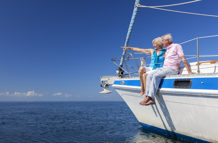 Photo pour A happy senior couple sitting on the side of a sail boat on a calm blue sea looking and pointing to a clear horizon - image libre de droit