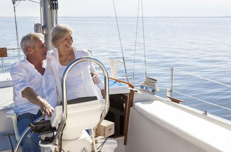 Foto de A happy senior couple sailing and sitting at the wheel of a sail boat on a calm blue sea - Imagen libre de derechos