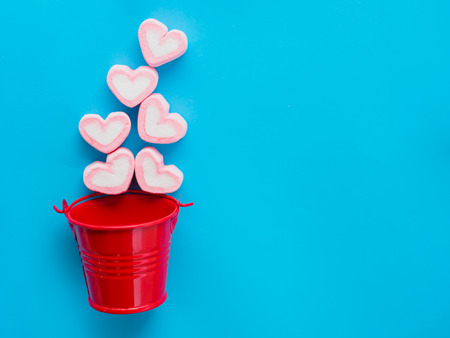 Photo for Marshmallow in a red bucket on Valentine's Day love concept on blue sky background - Royalty Free Image