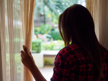 Photo for Rear view of a young woman holding the curtains open to look out of a large light window at home, interior. Positive and aspirational lifestyle. Sad Woman looking out a window, indoors. - Royalty Free Image