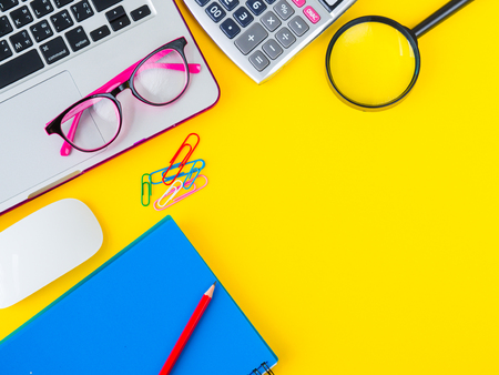 Photo for Flat lay, top view office table desk frame. feminine desk workspace with office accessories including calculator, mouse laptop, glasses, clips, Magnifying glass, cutter, note book and blue pen on yellow background. - Royalty Free Image