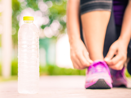 Photo pour Running shoes - closeup of water bottle and woman tying shoe laces. Female sport fitness runner getting ready for jogging in garden backgroound - image libre de droit