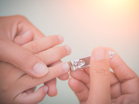 Foto de Family activity, soft focus of mother hand cut nails for kid by using nail clipper. - Imagen libre de derechos
