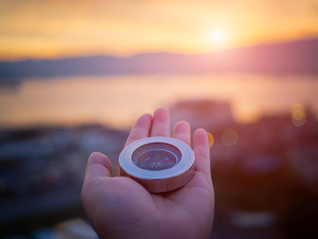 Foto de Closeup hand holding compass with  mountain and sunset sky background. - Imagen libre de derechos