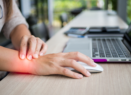 Foto de Closeup woman holding her wrist pain from using computer. Office syndrome hand pain by occupational disease. - Imagen libre de derechos