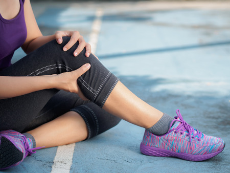 Foto de Young woman suffering from an ankle injury while exercising and running. Sport exercise injuries concept. - Imagen libre de derechos