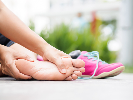 Photo pour Closeup woman massaging her painful foot while exercising.   Running sport injury concept. - image libre de droit