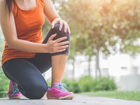 Photo pour Runner sport knee injury. Woman in pain while running in the garden. - image libre de droit