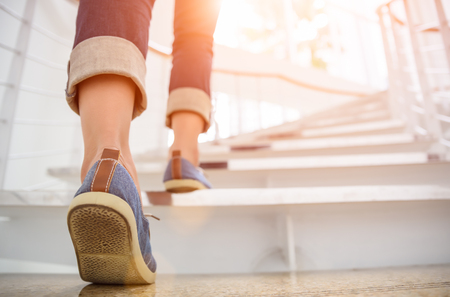 Photo pour Young adult woman walking up the stairs with sun sport background. - image libre de droit